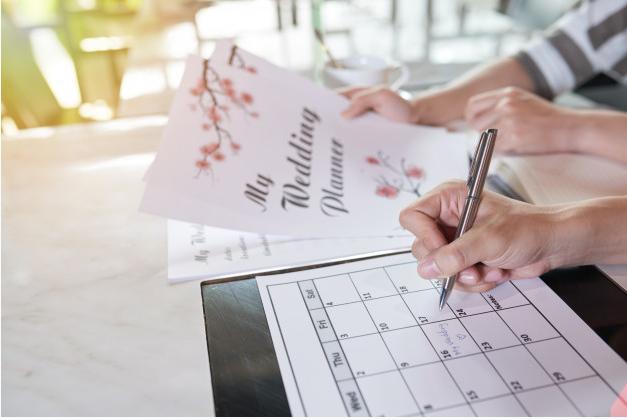 Casal pensando em como planejar um casamento com convites de casamento e calendário sendo marcado.