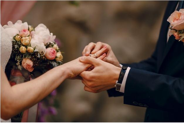 noivo colocando aliança na mão da noiva